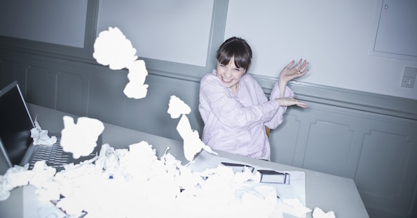 Young woman throwing crumpled paper