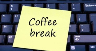 Coffee break written on a yellow post it note on a computer keyboard.