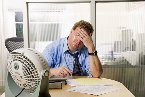Lavoratore soffre il caldo in ufficio. Occorre sistema di ventilazione adeguato